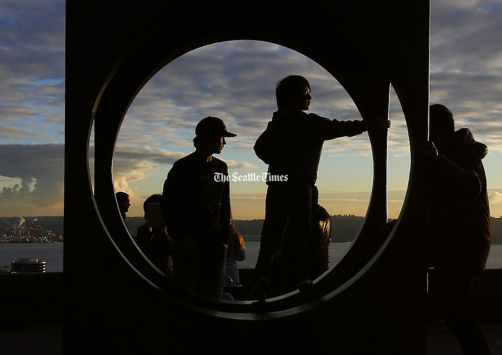 """Visitors to Seattle stand inside """"Changing Form,"""" a sculpture by Doris Chase, while gazing over the Puget Sound as the sun sets at Kerry Park in the Queen Anne neighborhood in Seattle. (Sy Bean / The Seattle Times)"""