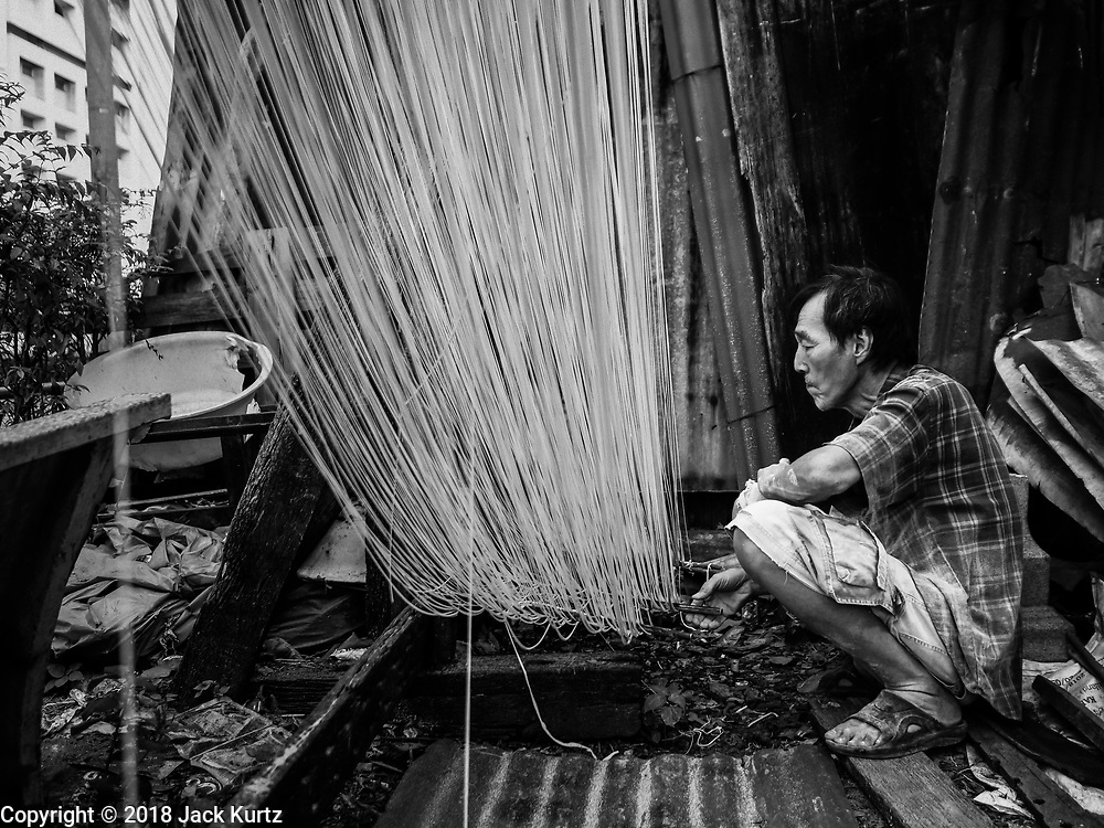 "29 DECEMBER 2018 - BANGKOK, THAILAND: A man hangs longevity noodles out to dry in front of his family shophouse. The family has been making traditional ""mee sua"" noodles, also called ""longevity noodles"" for three generations in their home in central Bangkok. They use a recipe brought to Thailand from China. Longevity noodles are thought to contribute to a long and healthy life and  are served on special occasions, especially Chinese New Year, which is February 4, 2019. These noodles were being made for Chinese New Year.    PHOTO BY JACK KURTZ"