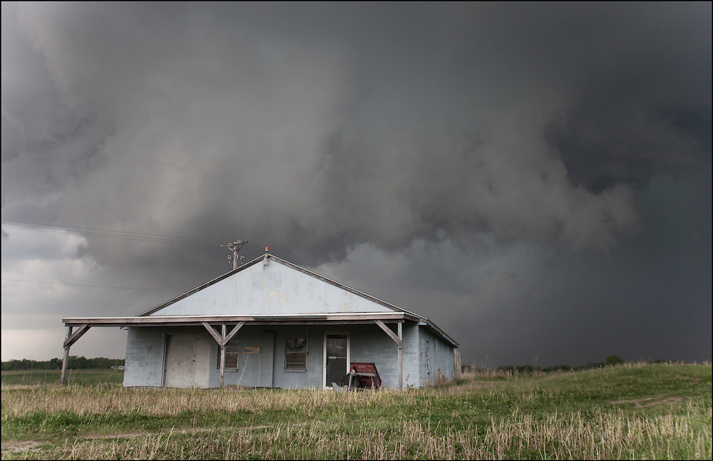 Rain wrapped tornado with a newly forming wall cloud over an abandoned store on Highway 24 near Wellington, Missouri.