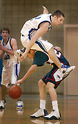 (ride-em-cowboy)  --  Zac Young's (12) mid-air acrobatics to avoid fouling Eisenhower's Jerad Groth (22) prove futile in WaHi's attempts to pull out a win against Eisenhower Saturday night at WaHi.        (2/05/05)        MATTHEW B ZIMMERMAN PHOTO
