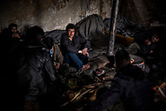 Migrants from Afghanistan are seen warming up in one of the abandoned wearhouses in Belgrade train station. Belgrade, Serbia. March 19th, 2017. Federico Scoppa