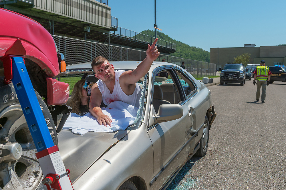 """Crash """"victim"""" Cameron Powell posses out a stray piece of glass before being part of a crash simulation outside of Riverside High Shcool. A team of public safety responders simulated a crash resulting from texting and driving<br /> for the students of Riverside High School in Belle, W.Va, on April 29, 2019. Responders from Belle Fire Department, Kanawha County Sheriff's Office, Kanawha County Emergency Management and Kanawha County Ambulance were on hand for the event."""