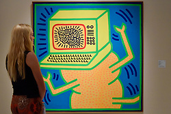 """© Licensed to London News Pictures. 28/06/2017. London, UK.  A visitor views """"Untitled, April 12, 1984"""" by Keith Haring.  Preview day at Masterpiece London, a leading art fair held in Chelsea, bringing together 150 international exhibitors presenting works from antiquity to the present day.  The event runs 29 June to 5 July 2017.   Photo credit : Stephen Chung/LNP"""