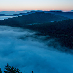 Fog rises from Echo Lake at dawn in Maine's Acadia National Park.