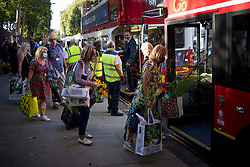 © Licensed to London News Pictures. 26/09/2021. London, UK. Members of the public board a bus carry exhibitors' plants on the last day of the 2021 Chelsea Flower show. A wide array of unusual and striking display items can be purchased on the closing day of The Royal Horticultural Society flagship flower show, held at the Royal Hospital in Chelsea since 1913. Photo credit: Ben Cawthra/LNP
