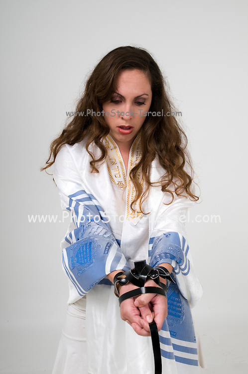 Religious Compulsion concept. Woman wrapped in leather straps resembling Phylacteries straps and Jewish prayer shawl (tallith)