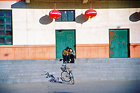 China, Taiyuan, 2008. Framed by the red lanterns of Chinese New Year, lovers take some time for themselves away from family concerns..