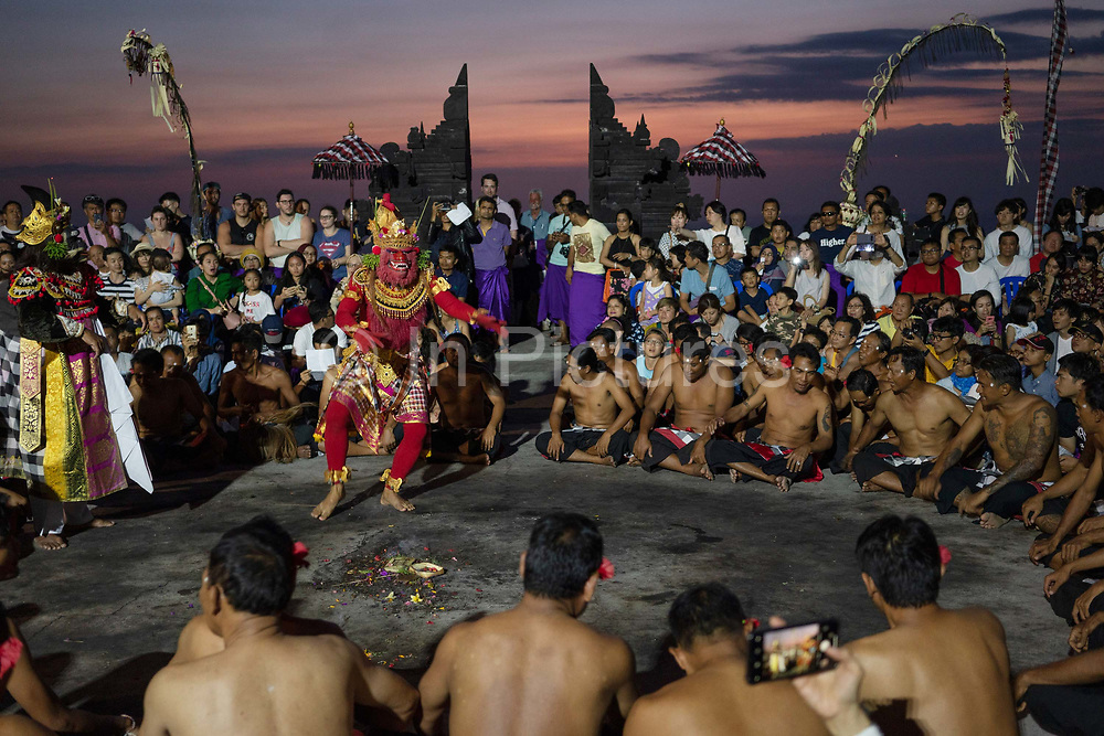 Dancers wearing traditional costumes participate in the Kecak fire dance, which takes place at the Pura Luhur Uluwatu Temple at the southernmost tip of the island on 17th June, 2018 in Bali, Indonesia. It is a sacredly positioned temple, believed to protect the island from evil spirits, and the fire dance performance is an adaptation of the Ramayana Hindu story.
