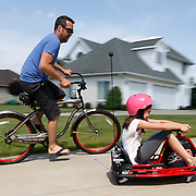 Sam Hornish Jr., a race car driver who has previously raced Indy Car and NASCAR, races around the driveway with daughter Addison, 10, in front of his home in Napoleon, Ohio, on Thursday, June 7, 2018.He is currently not racing, and is able to spend more time with his kids. Although he tried to convince his kids to race aroundthedriveway counterclockwise so they'd be making left turns, like during a stock car race,thekids chose to keep going clockwise.THEBLADE/KURT STEISS