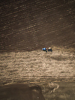 Aerial view of a tractor working on the farmland in Estonia.