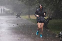 © Licensed to London News Pictures. 14/09/2021. London, UK. A woman jogs during heavy rain in Greenwich Park, South East London. A yellow weather warning for rain is in place in parts of England . Photo credit: George Cracknell Wright/LNP