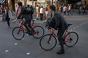 Two identical businessmen in grey suits ride matching bikes, pedalling through rush-hour traffic at London Bridge  on 8th September 2016, in Southwark, England UK.