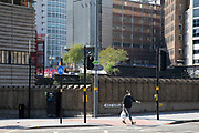 Woman wearing a surgical face mask in Birmingham city centre which is eerily quiet and deserted under lockdown due to Coronavirus on 24th April 2020 in Birmingham, England, United Kingdom. Coronavirus or Covid-19 is a new respiratory illness that has not previously been seen in humans. While much or Europe has been placed into lockdown, the UK government has extended stringent rules as part of their long term strategy, and in particular social distancing, which has left usually bustling areas like a ghost town.