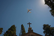 A passing jet airliner flies overhead, above the cross of a family mausoleum, on 14th July 2016, at Prazeres Cemetery, Lisbon, Portugal. Prazeres Cemetery Cemitério dos Prazeres is the largest cemetery in Lisbon, Portugal, located in the west part of the city in the former Prazeres parish. It was created in 1833 after the outbreak of a cholera epidemic. Many famous Portuguese citizens are buried here, including artists, authors and government figures, and the cemetery features many large mausoleums built in the 19th century.