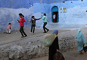 """Children play in Chefchaouen, Morocco, whose """"medina"""" (old city) is famous for its striking blue walls."""