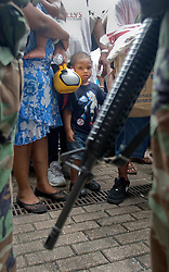 01 Sept, 2005. New Orleans, Louisiana.<br /> A young boy stares intently as troopers hold back the people from the Superdome. Thousands of desperate people mass outside the Superdome hoping for a seat on a bus to take them out of town to safety. Photo©; Charlie Varley/varleypix.com