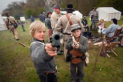 © London News Pictures. 08/04/2012. South Okendon, UK.  Cousins Bailey HAskett aged 10 (left and Kiri Haskett, aged 11 (right) play with replica guns dressed as Confederate soldiers  before taking part in a reenactment of the final days of the American Cival war at Belhus Wood Country Park near South Okenden, Essex on April 8, 2012. The American Civil war was ended on April 9 (Tomorrow), 1865 when the  Confederate surrendered to the Union. Photo credit :  Ben Cawthra/LNP