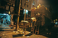 In the cooler night air workers load a truck in the backstreets of Guangzhou, Guangdong Province, China.
