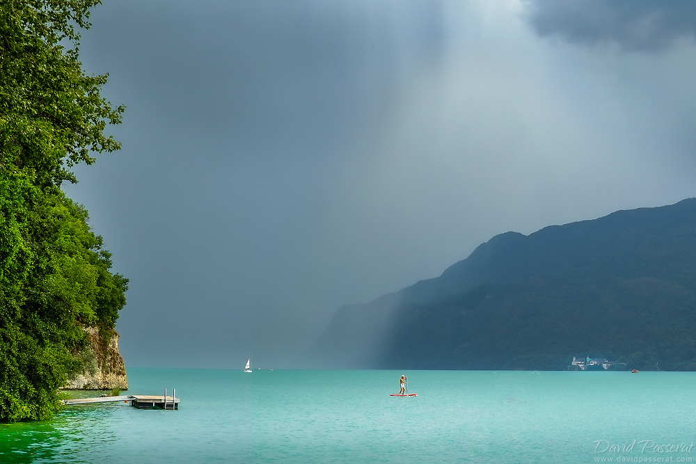 Coming storm over the lake with man on a paddle in distance.