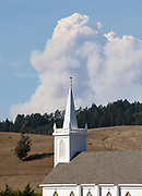 A massive smoke culumn from the Walbridge Fire rises into the sky above St. Theresa of Avila Church in Bodega, California on August 19, 2020.