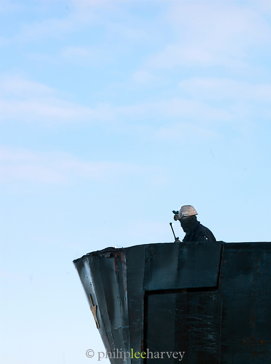 A welder repairs the hull of a ship in the dock at Tromso, Norway
