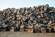 A mountain of aluminum bricks, made from squashed drink cans, awaiting redistribution to Thailand or Vietnam for recycling. This warehouse operates big distribution for aluminium cans, and general metals, on the edge of Phnom Penh. Aluminium cans are sold with a street value of about 1$ the kilo, the small warehouse add 10% and all the cans are shipped. already sorted to the big distribution recycling warehouses outside Phnom Penh. Here the aluminium cans are squashed into bricks and stacked or placed in mountains for export to Thailand and Vietnam for truning back into the raw material.