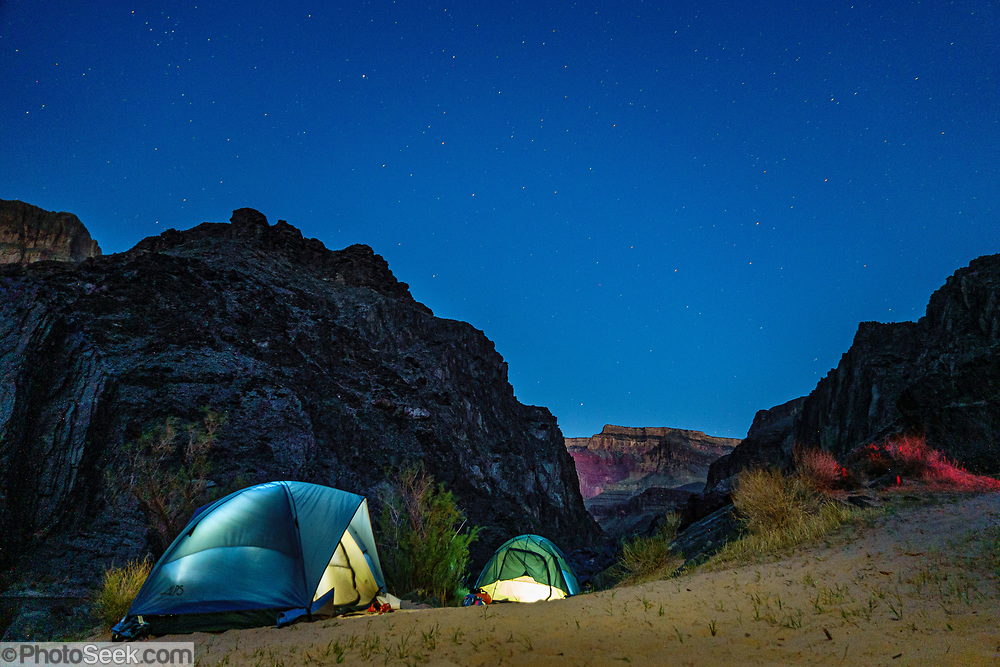 Tents glow at night under the stars in Schist Camp in the Inner Gorge of Grand Canyon at Colorado River Mile 96.5 (measured downstream from Lees Ferry). Day 6 of 16 days rafting 226 miles down the Colorado River in Grand Canyon National Park, Arizona, USA.