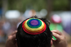 "© Licensed to London News Pictures . 03/06/2016 . Tel Aviv , Israel . A man wearing a rainbow skullcap . Over 100,000 people attend the gay pride parade in Tel Aviv , reported to be the largest such event in the Middle East and Asia . The Israeli government has been accused of using the event as "" pinkwashing "" , marketing the event in order to deflect accusations of poor human rights behaviour . Photo credit: Joel Goodman/LNP"
