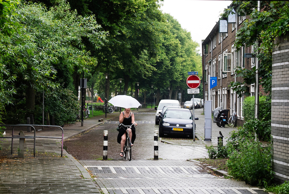 In Utrecht rijdt een vrouw op de fiets door de regen met een paraplu.<br /> <br /> In Utrecht cyclists a woman cycles in the rain with an umbrella.