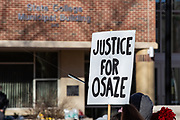 """A protester holds a sign demanding """"justice for Osaze"""" in State College, Pennsylvania on March 19, 2021. The 3/20 Coalition organized a protest and march to mark the second anniversary of Osaze Osagie being shot and killed by State College police at his apartment. (Photo by Paul Weaver)"""