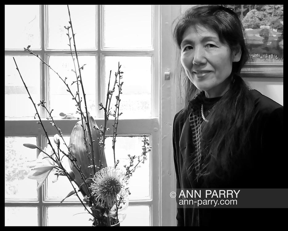 Manhasset, New York, U.S., April 8, 2018. Artist poses behind her flower arrangement in vase at Reception for The Art Guild exhibition is held at Elderfields Preserve.