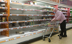 © Licensed to London News Pictures. 07/10/2021. London, UK. A shopper wearing a face covering at nearly empty shelves of pre-cooked meat products in Sainsbury's, north London just after 9am. The Government and retailers warn that food and fuel shortages could continue until Christmas due to labour shortages following Brexit. Photo credit: Dinendra Haria/LNP
