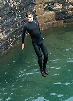 Facemask Tombstoning off the Port Walls in Charlestown near St Austell Bay Cornwall  photo Brian Jordan