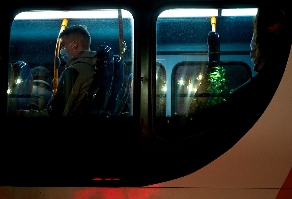 A man waits for the bus to leave from Cheltenham high street on the night before the UK's second lockdown due to covid-19 on 2nd November 2020.