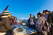 Indian tourists inspect the postcards and calendars for sale at a vendors table in the Himalayan foothills,