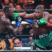 Luis Ortiz lands a straight right to the head of Deontay Wilder during the WBC Heavyweight Championship boxing match at Barclays Center on Saturday, March 3, 2018 in Brooklyn, New York. Wilder would win the bout by knockout in the tenth round to retain the title and move to 40-0. (Alex Menendez via AP)