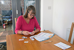 Woman taking part in UK Biobank's research into Coronavirus.  Each month for six months she will take a blood sample which will be tested for Covid-19 antibodies. UK May 2020. Posed by model