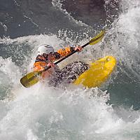 Play boat kayaker Bryce Shaw (MR) wave surfing on Kananaskis River, Kananskis Provincial Park, near Banff and Calgary, Alberta, Canada