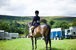 © Licensed to London News Pictures.15/08/15<br /> Rosedale, UK. <br /> <br /> A competitor sits on her horse before entering the arena to compete during the Rosedale Country Show. This mainstay annual event remains as popular as ever attracting visitors and entrants from across the region.<br /> <br /> Photo credit : Ian Forsyth/LNP