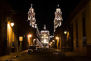 A quiet street at night leads to the large baroque cathedral of Morelia, Michoacan State, Mexico.