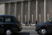 Businessmen below the tall pillars of the Bank of England on Threadneedle Street, pass between black taxi cabs on 10th May 2017, in the City of London, England.