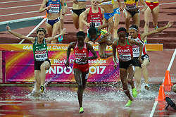 London, August 09 2017 . Birtukan Fente, Ethiopia, takes a tumble as Ruth Jebet, Bahrain, and Beatrice Chepkoech, Kenya, take the lead, closely followed by Amina Bettiche, Algeria, in the women's 3,000m steeplechase heats on day six of the IAAF London 2017 world Championships at the London Stadium. © Paul Davey.