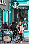 A young woman seating on a bicycle is seen queuing outside a Starbucks coffee shop in the city centre of Belfast on Sunday, April 25, 2021. (Photo/ Vudi Xhymshiti)