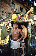 YOUTHS SHOWER WITH BUCKET. Rocinha Favela, Rio de Janeiro, Brazil, South America. Men washing themselves outside with buckets of water. Although Rocinha is technically classified as a neighborhood, many still refer to it as a favela. It developed from a shanty town into an urbanized slum. Today, almost all the houses in Rocinha are made from concrete and brick. Some buildings are three and four stories tall and almost all houses have basic sanitation, plumbing, and electricity. Compared to simple shanty towns or slums, Rocinha has a better developed infrastructure and hundreds of businesses. There is also lots of deliquency, crime and drugs in the favelas.