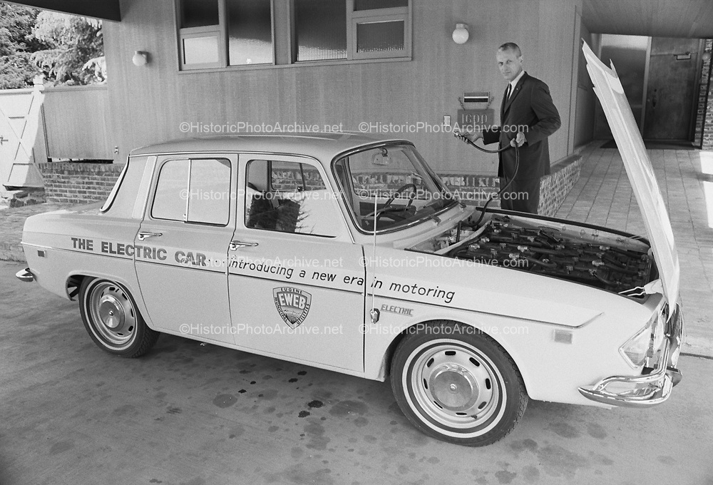 """1006-A451-27A. """"Electric car. in traffic & garage, for brochure. April 1968"""" (1968 MARS II : 1967 Renault R-10. This 4-seater was produced as one of a series of 42. Purchased by Eugene, Oregon's local electric utility ( EWEB ), this car has all of its original components intact. The MARS II production run of 42 was the beginning of the 2nd generation of electric vehicles. This car is most likely the only remaining vehicle with its original equipment intact. Most notable is the MARS II's mechanical controller board that preceded the electronic controllers of the later generations of electric cars. The MARS II is a 120 volt system.)"""