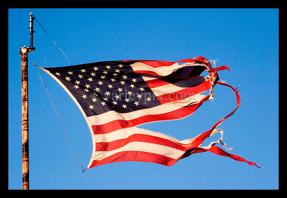 4th Feb, 2006. New Orleans, Louisiana. An American flag, ripped and damaged by hurricane Katrina recieves a follow up battering from a tornado which smashed through River Bend in uptown New Orleans a few days earlier. The city may be down, but the flag still flies over New Orleans.