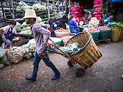 17 MAY 2013 - BANGKOK, THAILAND:   A porter pulls a handtruck through the vegetable section of the flower market in Bangkok. The Bangkok Flower Market (Pak Klong Talad) is the biggest wholesale and retail fresh flower market in Bangkok. It is also one of the largest fresh fruit and produce markets in the city. The market is located in the old part of the city, south of Wat Po (Temple of the Reclining Buddha) and the Grand Palace.   PHOTO BY JACK KURTZ