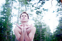"""Man in yoga posture outdoors in the forest.<br /> :::<br /> """"The world is holy. We are holy. All life is holy. Daily prayers are delivered on the lips of breaking waves, the whisperings of grasses, the shimmering of leaves.""""<br /> <br /> ~ Terry Tempest Williams"""