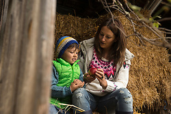 Mother and son sitting on straw in the stable, Bavaria, Germany