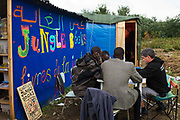 France , Calais, camp for refugees known as 'The Jungle'. September 21st 2015. A group of Sudanese men study English with a volunteer outside the library, Jungle Books.